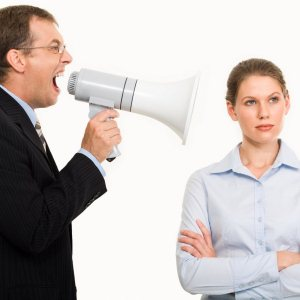 Portrait of angry boss shouting at his secretary through megaphone who is indifferent to it